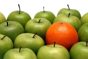 different concepts - orange between green apples